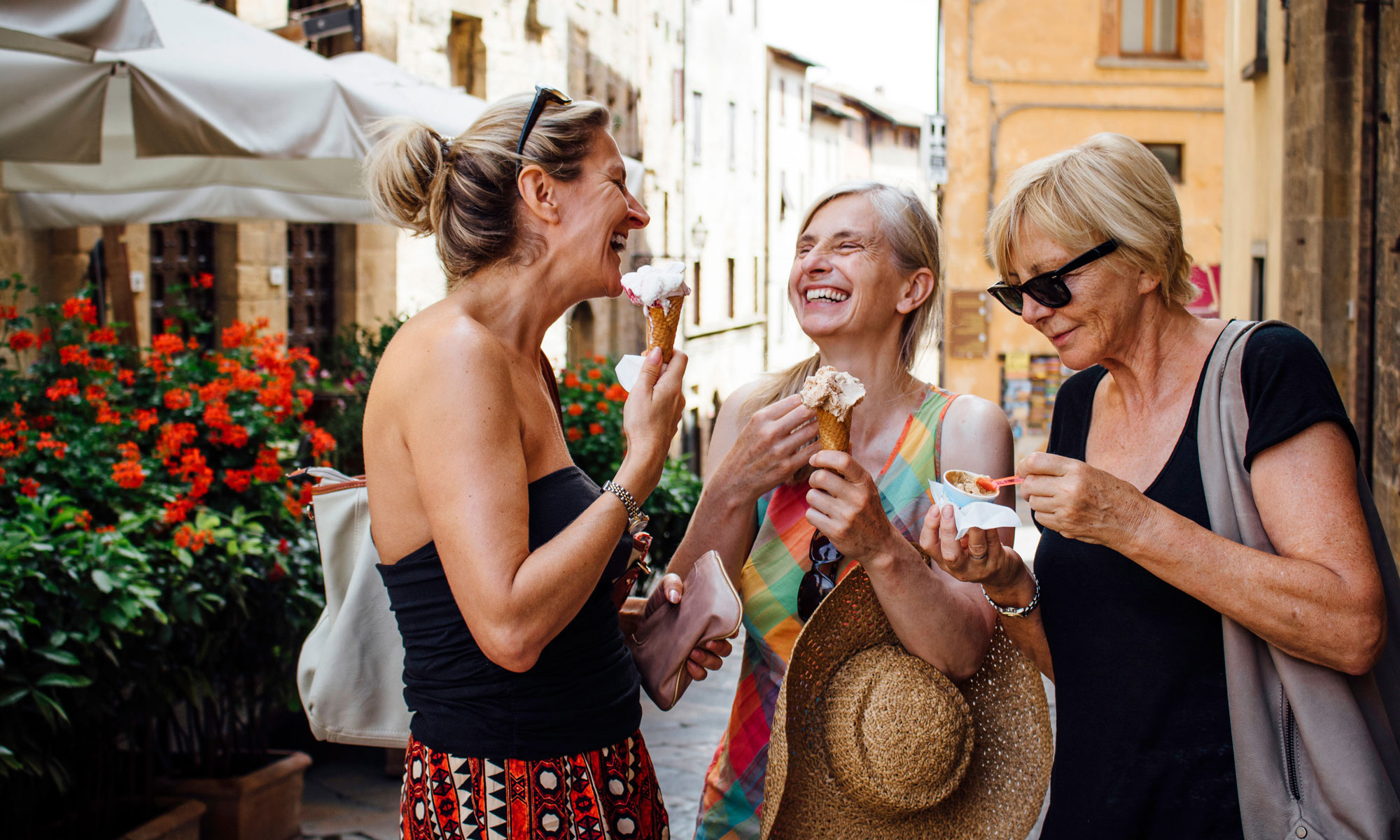 Three happy women eating icecream in town.